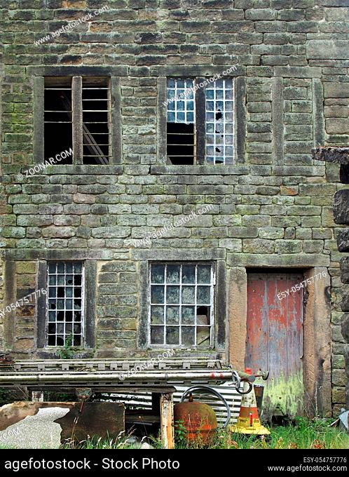 the facade of an old derelict stone house with broken windows and peeling red door with junk outside the front