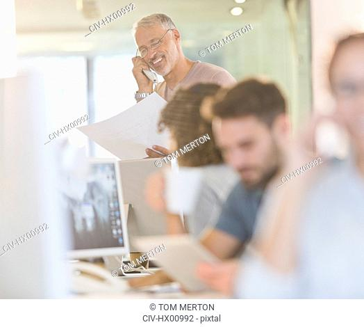 Architect with blueprints talking on telephone in office