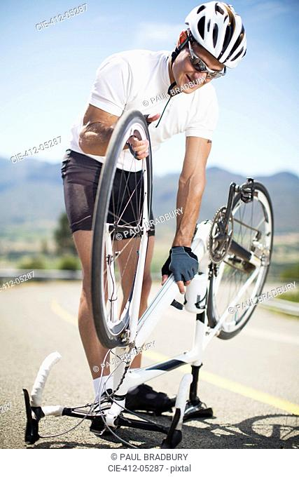 Man adjusting bicycle on rural road