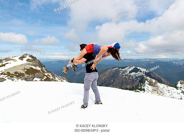 Man carrying woman over shoulder on mountain-top, Silver Star Mountain, Washington, USA