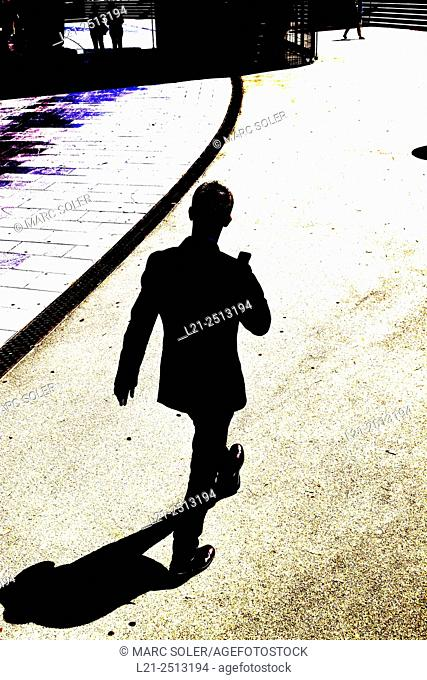Silhouette of a man walking and holding a mobile phone