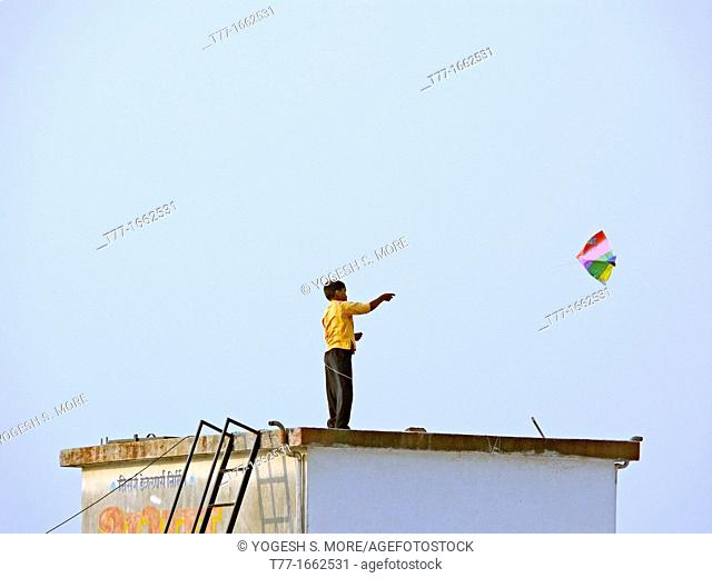A boy playing with a kite, kite in flight Pune, Maharashtra, India