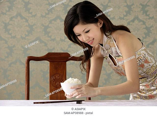 Young woman placing bowl of rice on table