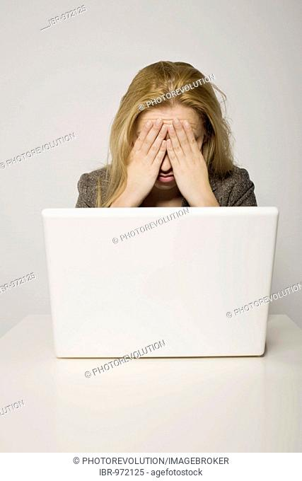 Young long-haired woman sitting frustatedly in front of her computer, notebook, her hands covering her face