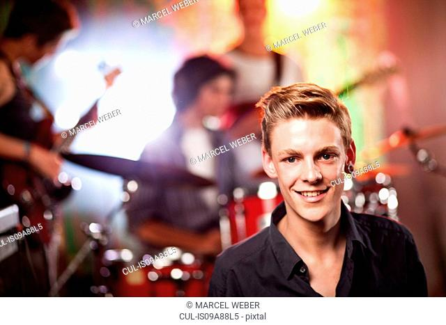 Teenagers at concert, young man in foreground