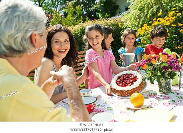 Germany, Bavaria, Family having coffee and cake in garden, smiling