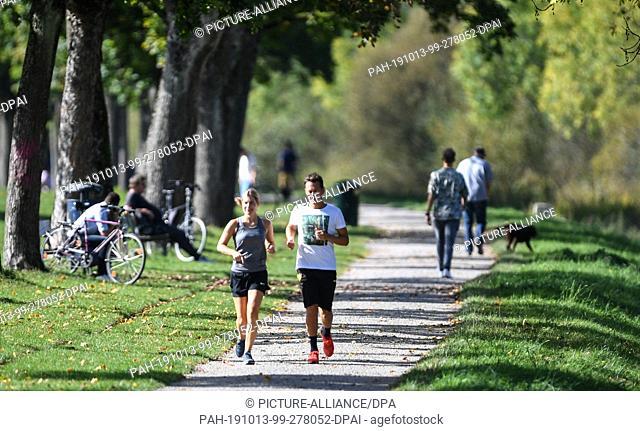 13 October 2019, Baden-Wuerttemberg, Freiburg: Niklas and Rositta jog in the sunshine past the Dreisam at trees. Photo: Patrick Seeger/dpa
