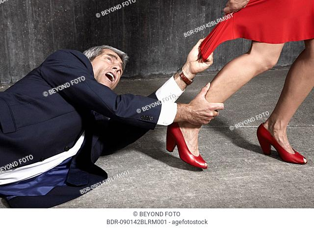 desperate man lying on floor trying to hold woman