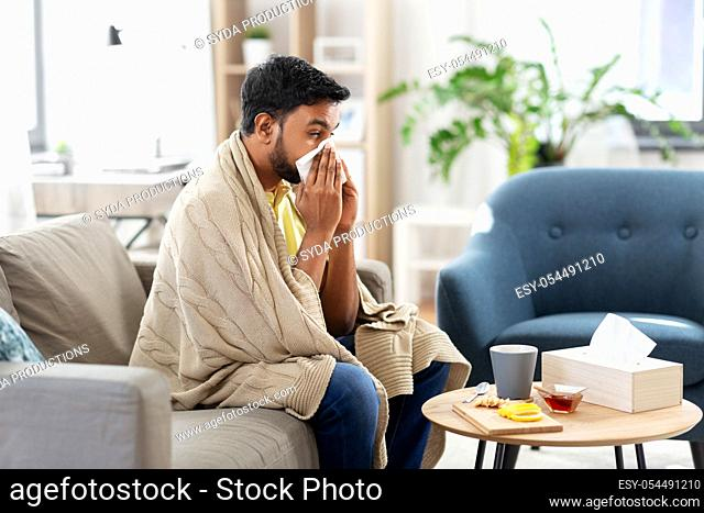 sick man blowing nose in paper tissue at home