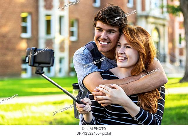 A young couple standing together in a university campus and taking a selfie with a smart phone on a selfie stick; Edmonton, Alberta, Canada