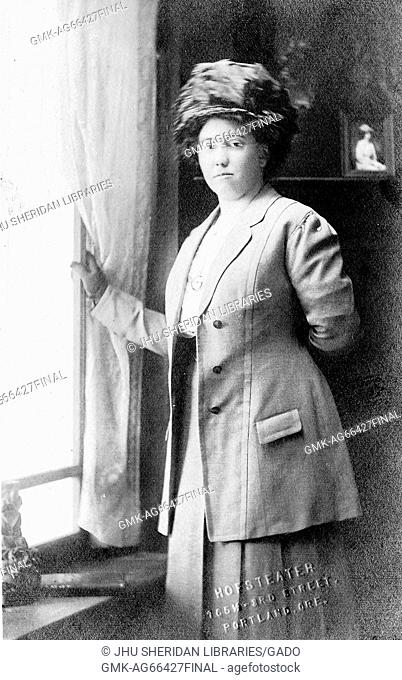 Portrait of an African American woman standing next to a window, wearing a hat, glasses and a two-piece jacket and skirt