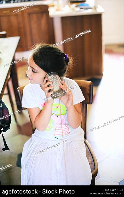 Little girl in the house playing with the phone acoustic string
