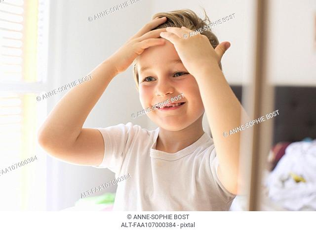 Boy fixing hair in front of mirror