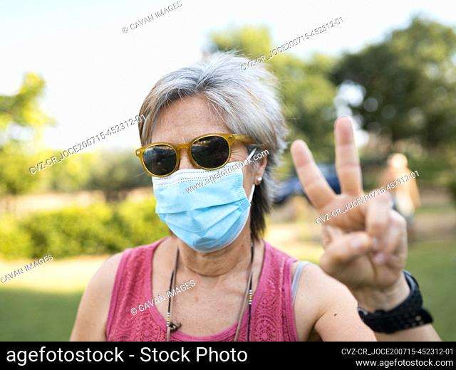 pretty white hair senior woman with mask by covid-19, victory symbol with hand