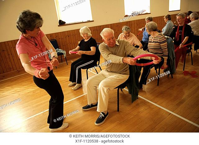 senior citizens participating in a low-impact chair aerobics class in a small village hall in west wales UK