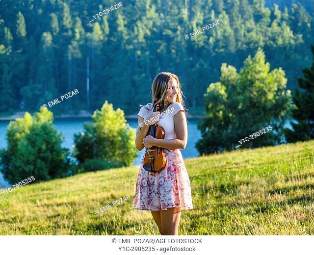 Attractive musician young female violinist in nature near lake. Croatia