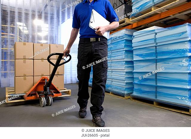 Worker on loading dock pulling inventory on hand truck