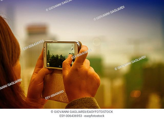 Woman taking city picture with her smartphone