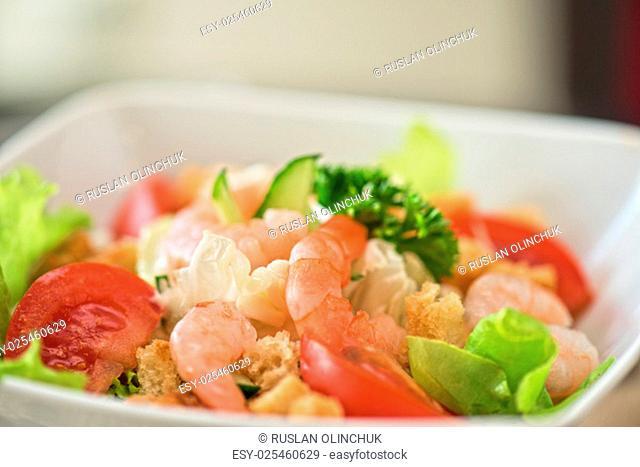 Caesar shrimp salad with cheese and arugula