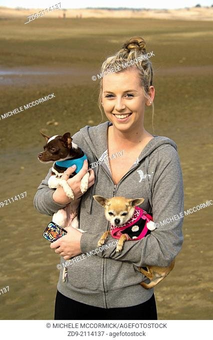 A pretty girl carries to chihuahuas as she explores the dry Folsom lakebed