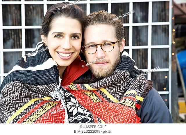 Couple wrapped in blanket outdoors