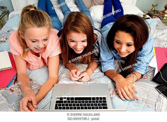 Teenage girls looking at laptop