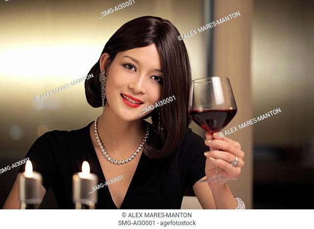 Young woman drinking wine during a candle lit dinner