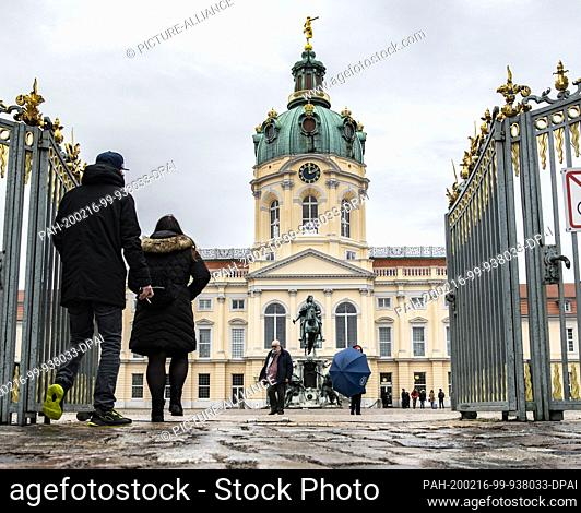 16 February 2020, Berlin: On this rainy and windy Sunday, passers-by walk through the entrance gate of Charlottenburg Palace. Photo: Paul Zinken/dpa