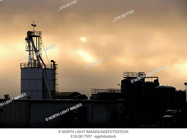 USA, California. Industrial building silhouetted against orange clouds and setting sun