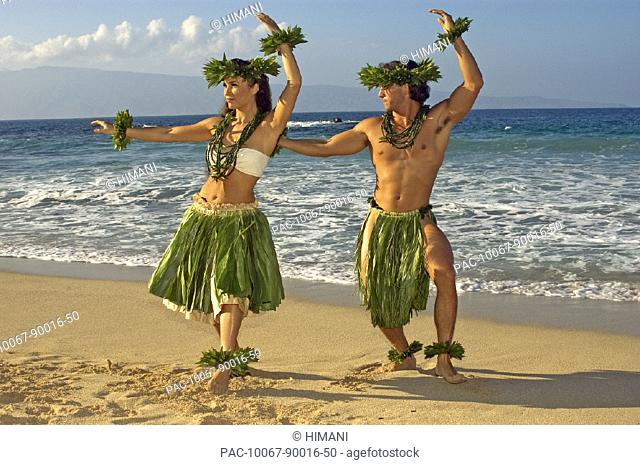 Male and female hula dancers in ti-leaf, haku, lei, in a dancing pose on the beach