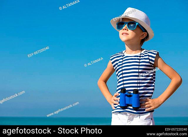 One happy little boy playing on the beach at the day time. He are dressed in sailor's vest. Kid having fun outdoors. Concept of sailor on vacation
