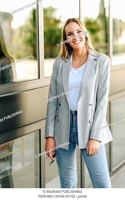 Beautiful young caucasian woman smiling in urban background. Blond girl wearing casual clothes in the street. Female with elegant jacket and blue jeans