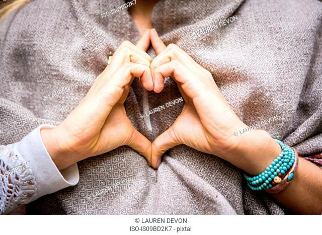 Young woman's hands making heart shape, cropped