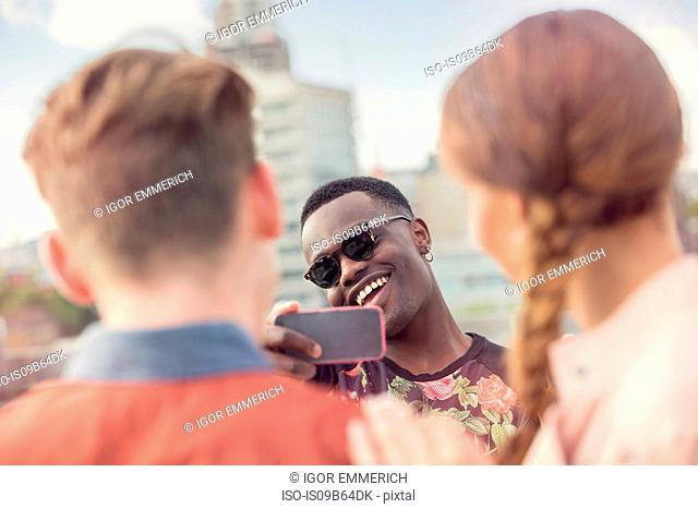 Young man photographing friends at roof party in London, UK