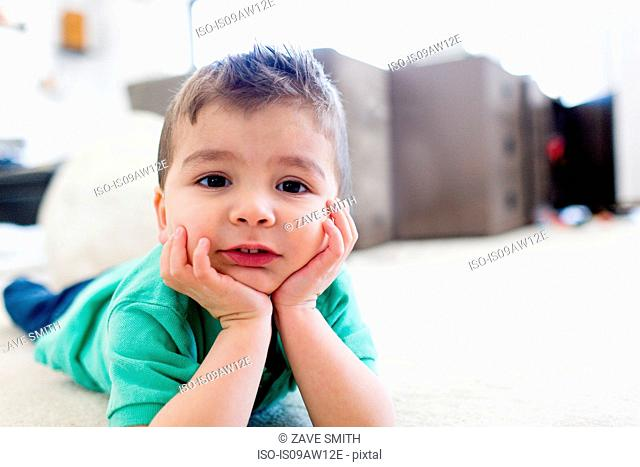 Preschool boy lying on carpet chin in hands, resting on elbows, looking at camera
