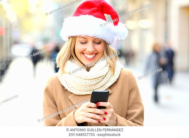 Happy woman wearing santa hat reading phone text on christmas in the street