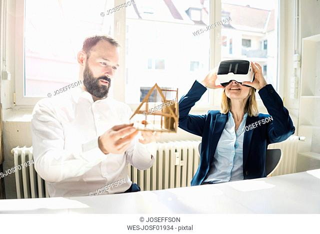 Woman and man with house model and VR glasses in office