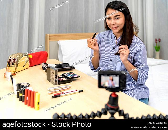 Young beautiful Asian woman beauty vlogger blogger recording live make up tutorial share on social media using digital camera on tripod