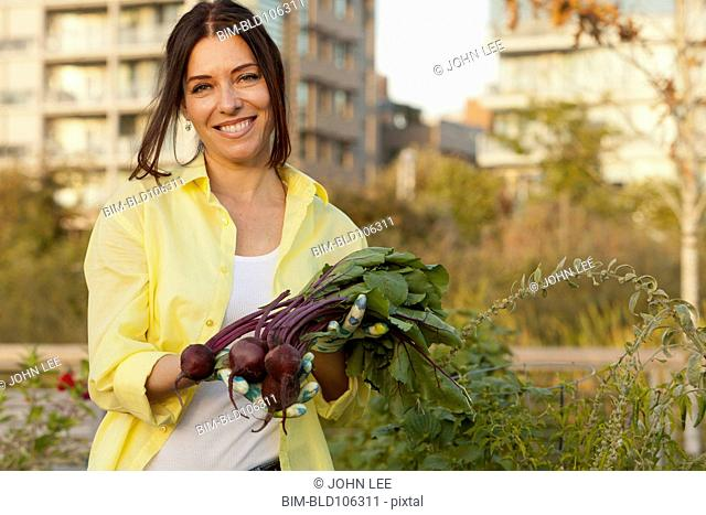 Caucasian woman holding bunch of beets