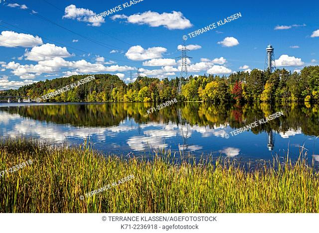 The calm water of the Sainte Maurice River reflecting colorful fall foliage in Shawinigan, Quebec, Canada