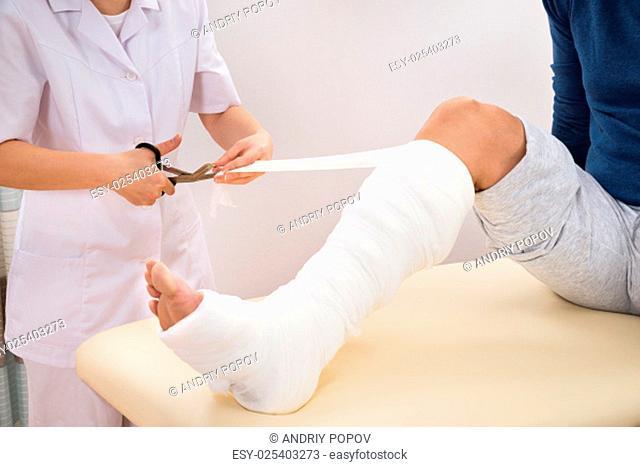 Portrait Of Female Doctor Bandaging Patient's Leg In Clinic