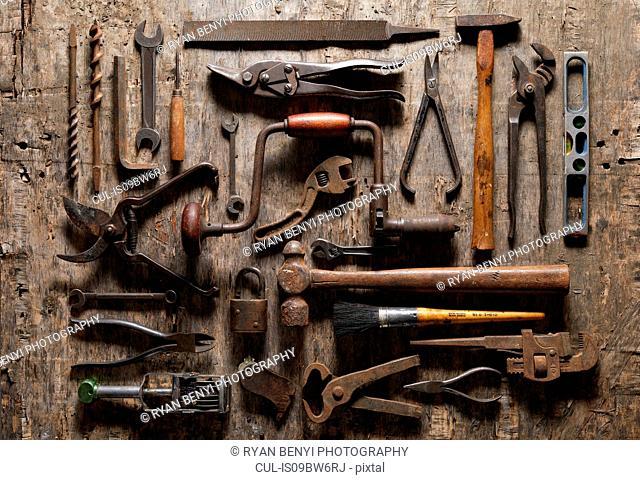 Variety of vintage hand tools on wood, overhead view