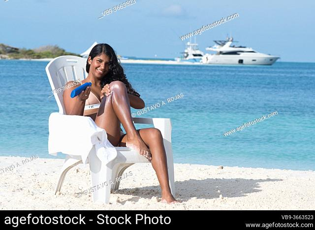 YOUNG African American WOMAN apply sunscreen LOTION AT TROPICAL BEACH on the beach chair