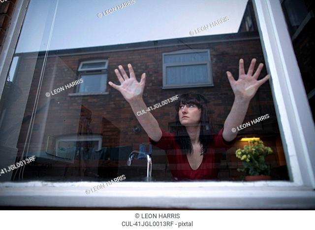 Woman in kitchen leaning on window