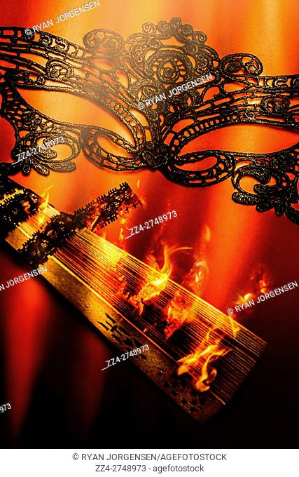 Fire lit wooden fan and performing arts mask on bright lit orange background. Masquerade of passion