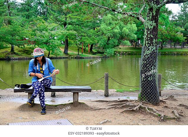 Thai woman looking map at the garden of Todai-ji Temple in Nara, Japan