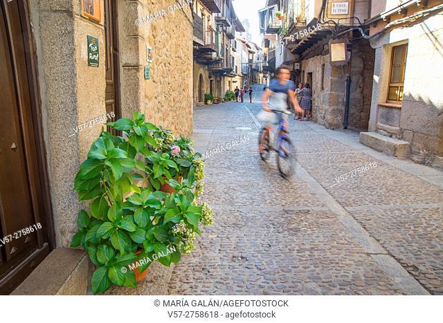 Street and boy riding a bike. Miranda del Castañar, Sierra de Francia Nature Reserve, Salamanca province, Castilla Leon, Spain