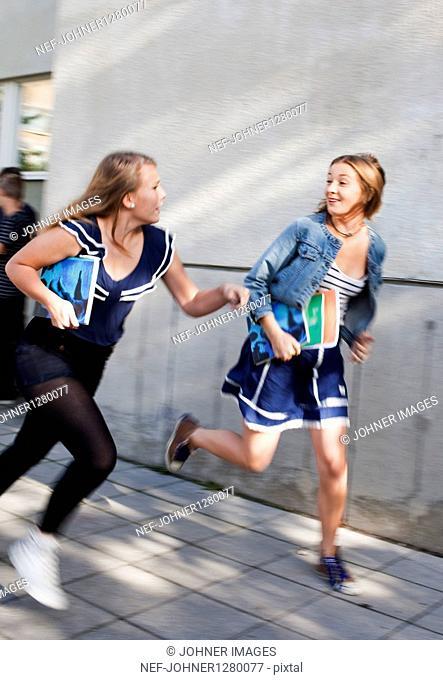 Two teenage girls running outside school