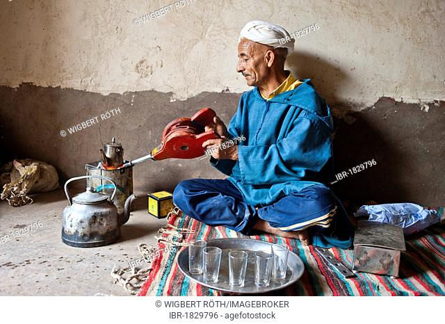Elderly Berber man wearing a turban sitting on the floor on a rug preparing traditional mint tea, kindling the fire in a little tin stove with a blower