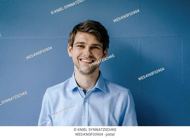 Portrait of smiling man in front of blue wall
